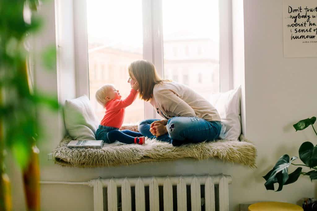 Madre e hijo jugando cerca a la ventana